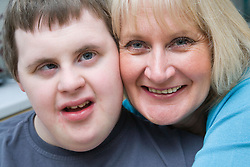 Mother and teenage son with Downs Syndrome having a cuddle,