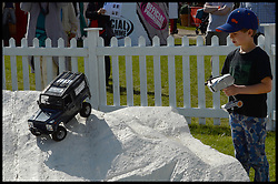 The Earl and Countess of Wessex  son James, Viscount Severn playing on the remote control land rovers  at the Royal Windsor Horse Show. Windsor, United Kingdom. Wednesday, 14th May 2014. Picture by Andrew Parsons / i-Images