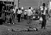 A Haitian boy covers his mouth as he walks past the body of another dead man left in the street as a warning not to allow Arisitide's return.