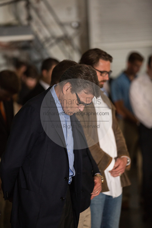 Former Texas Governor and GOP presidential hopeful Rick Perry bows his head in prayer before holding a town hall aboard the USS Yorktown June 8, 2015 in Mount Pleasant, South Carolina.