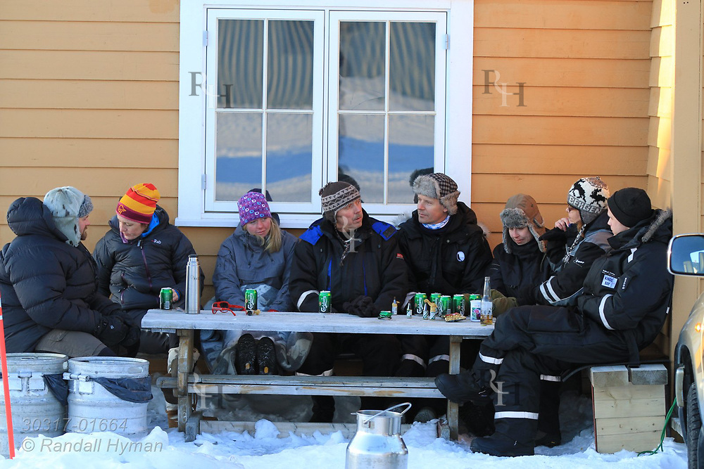 Scientists and workers socialize and drink beers in winter coats outside research stations at the international science village of Ny-Alesund on Spitsbergen island in Kongsfjorden; Svalbard, Norway.