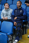 AFC Wimbledon defender Rod McDonald (4) injured and AFC Wimbledon midfielder Dylan Connolly (16) watching the game during the EFL Trophy (Leasing.com) match between AFC Wimbledon and U23 Brighton and Hove Albion at the Cherry Red Records Stadium, Kingston, England on 3 September 2019.