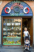 Shopper at Fabbrica Taddeucci patisserie shop and cafe in Piazza San Michele, Lucca, Italy