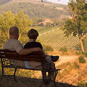 Couple sits on bench overlooking fields and vineyards near Villa Rosa agriturisimo, Panzano in Chianti, Italy - no release available<br />