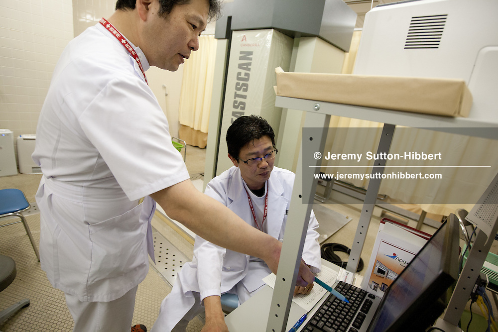 Tomoyoshi Oikawa (on left of photo), Assistant Director at Minami-Soma Municipal General Hospital, speaks with a colleague next to a full body scanner which scans patients for internal nuclear radiation contamination, in Minami-Soma, Japan, on Thursday 16th February 2012.