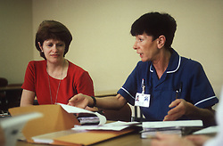 Two health workers sitting around table undergoing staff development training at the Queens Medical Centre; Nottingham,