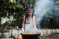 "ROME, ITALY - 3 JULY 2016: Gipsy Queens member Micescu Mieila (49) grills meat at their food stand at the iFest, an alternative music festival  in Rome, Italy, on July 3rd 2016.<br /> <br /> The Gipsy Queens are a travelling catering business founded by Roma women in Rome.<br /> <br /> In 2015 Arci Solidarietà, an independent association for the promotion of social development, launched the ""Tavolo delle donne rom"" (Round table of Roma women) to both incentivise the process of integration of Roma in the city of Rome and to strengthen the Roma women's self-esteem in the context of a culture tied to patriarchal models. The ""Gipsy Queens"" project was founded by ten Roma women in July 2015 after an event organised together with Arci Solidarietà in the Candoni Roma camp in the Magliana, a neighbourhood in the South-West periphery of Rome, during which people were invited to dance and eat Roma cuisine. The goal of the Gipsy Queen travelling catering business is to support equal opportunities and female entrepreneurship among Roma women, who are often relegated to the roles of wives and mothers."