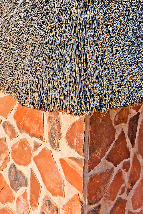 Typical architectural textures in Africa tourism spots. Grass thatch roof with stone wall. The stone work reminds me of a Giraffe.
