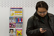 A Japanese man checks his smart phone in Bic Camera electronics store in front of a sign informing customers that they can pay with Bitcoins. Akihabara, Tokyo, Japan. Friday January 26th 2018. Japan elevated crypto-currencies  to the same status as other forms of money in March 2016 then in April 2017 allowed businesses to use Bitcoin as a legitimate form of payment. This led to large value hikes on this digital currency. Investing and using Bitcoins continues to gain popularity in Japan despite recent drops in their trading value..