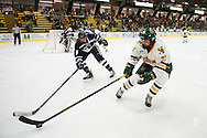 Vermont's Taylor Willard (27) battles for the puck with New Hampshire's Julia Fedeski (5) during the women's hockey game between the New Hampshire Wildcats and the Vermont Catamounts at Gutterson Field House on Friday night February 3, 2017 in Burlington. (BRIAN JENKINS/for the FREE PRESS)