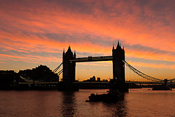 © Licensed to London News Pictures. 03/10/2016. LONDON, UK.  Colourful pink sky is seen just before sunrise behind Tower Bridge on the River Thames in London this morning. Sunshine and warm autumn weather are forecast for today.  Photo credit: Vickie Flores/LNP