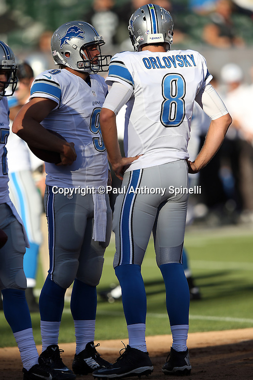 Detroit Lions quarterback Dan Orlovsky (8) talks to Detroit Lions quarterback Matthew Stafford (9) before the 2014 NFL preseason football game against the Oakland Raiders on Friday, Aug. 15, 2014 in Oakland, Calif. The Raiders won the game 27-26. ©Paul Anthony Spinelli