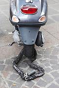 Motor scooter locked with a massive chain against theft.Motorroller mit einer massiven Kette vor Diebstahl gesichert