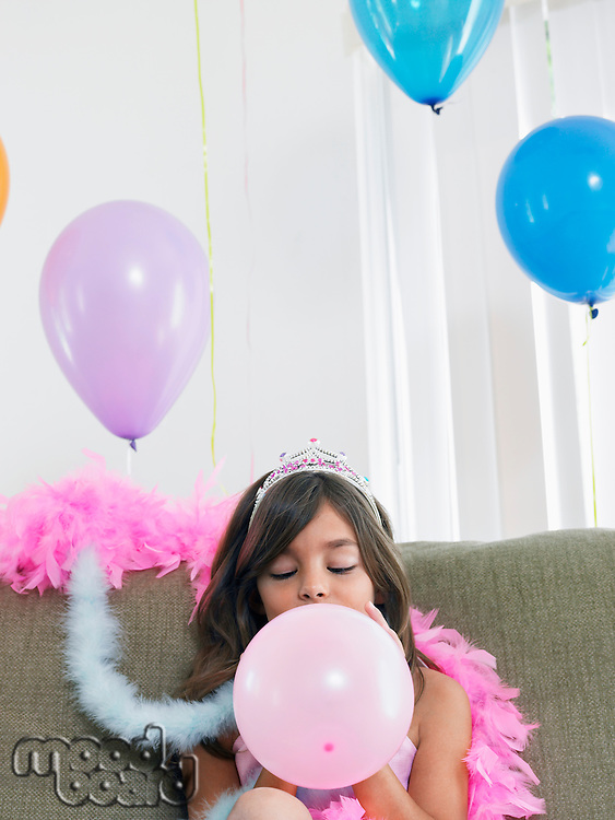 Young girl (7-9) sitting on sofa blowing up balloon