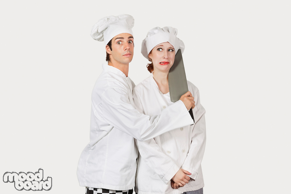 Portrait of male chef attacking female colleague with a cleaver against gray background