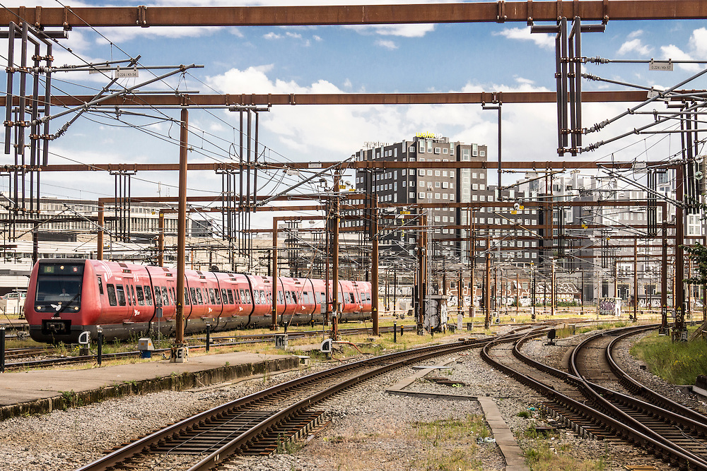A red Danish S Train (S-tog) run by Danske Stats Bane (Danish State Railway) - otherwise known as DSB. The train is seen pulling in to Copenhagen's Central Station (Hovedbanegården), with the WakeUp hostel and several other buildings in the background.