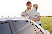 Romantic young couple leaning on car during road trip
