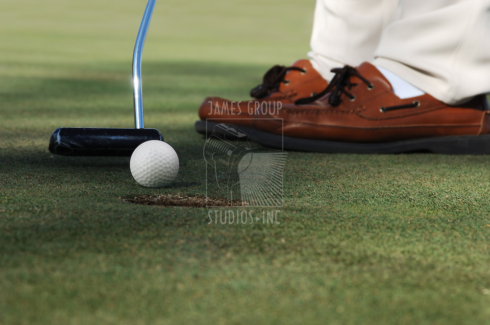 worm's eye, close-up of golf ball, putter and golfer's shoes on a putting green