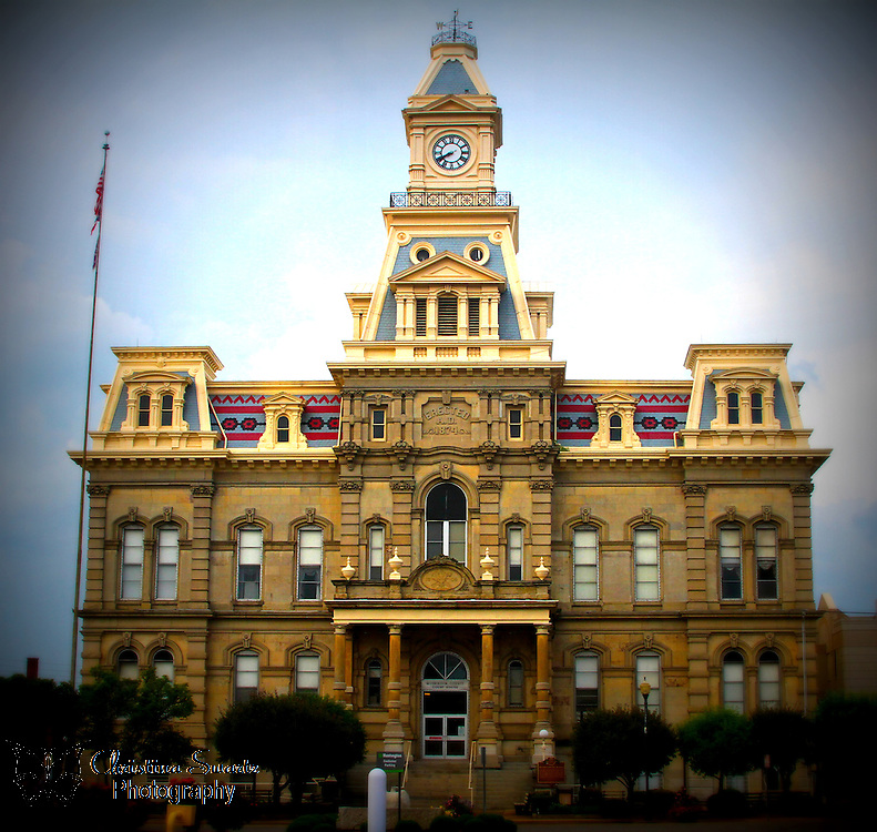 The Muskingum County Courthouse image for sale. The Muskingum County Courthouse is a historic building in Zanesville, Ohio. It was designed by T.B. Townsend and H. E. Myer, and built in 1877 with stone, brick, and slate in the Second Empire architecture style. The building is listed on the National Register of Historic Places and is located at 4th and Main Streets.[2]<br />  <br /> The site served as the capitol of Ohio from October 1, 1810, until May 1, 1812, and the 9th and 10th sessions of the Ohio General Assembly met here at the building that was formerly at the site before those sessions were returned to Chillicothe in May 1812. The former building on the site was then used as the Muskingum County Courthouse until current one was constructed in 1874. The 1809 date stone from the old building was incorporated into the new building and may be seen over the front steps.