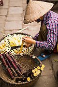 09 APRIL 2012 - HANOI, VIETNAM:  A pineapple vendor cuts fruit on a street in Hanoi, the capital of Vietnam. Hanoi, established in 1010 AD, is one of the oldest permanent cities in Southeast Asia. PHOTO BY JACK KURTZ