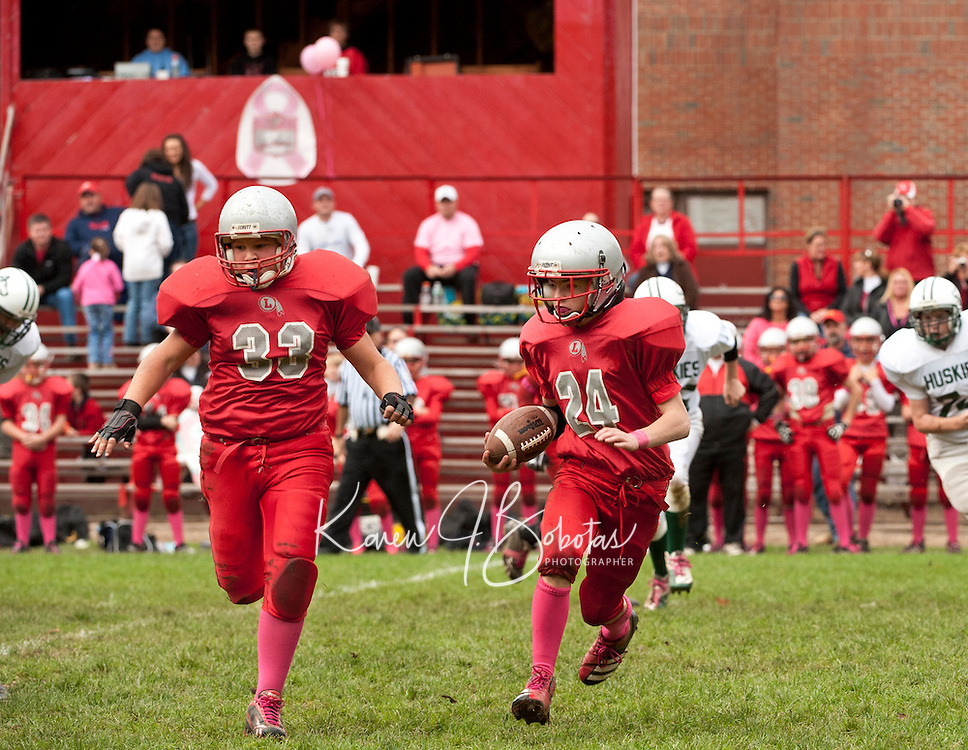 """Donning """"pink socks"""" in dedication and to raise funds and awareness for Breast Cancer Research Carter Doherty and Kyle Chiasson make a play for Laconia Middle football against Monadnock Saturday morning.  (Karen Bobotas/for the Laconia Daily Sun)"""