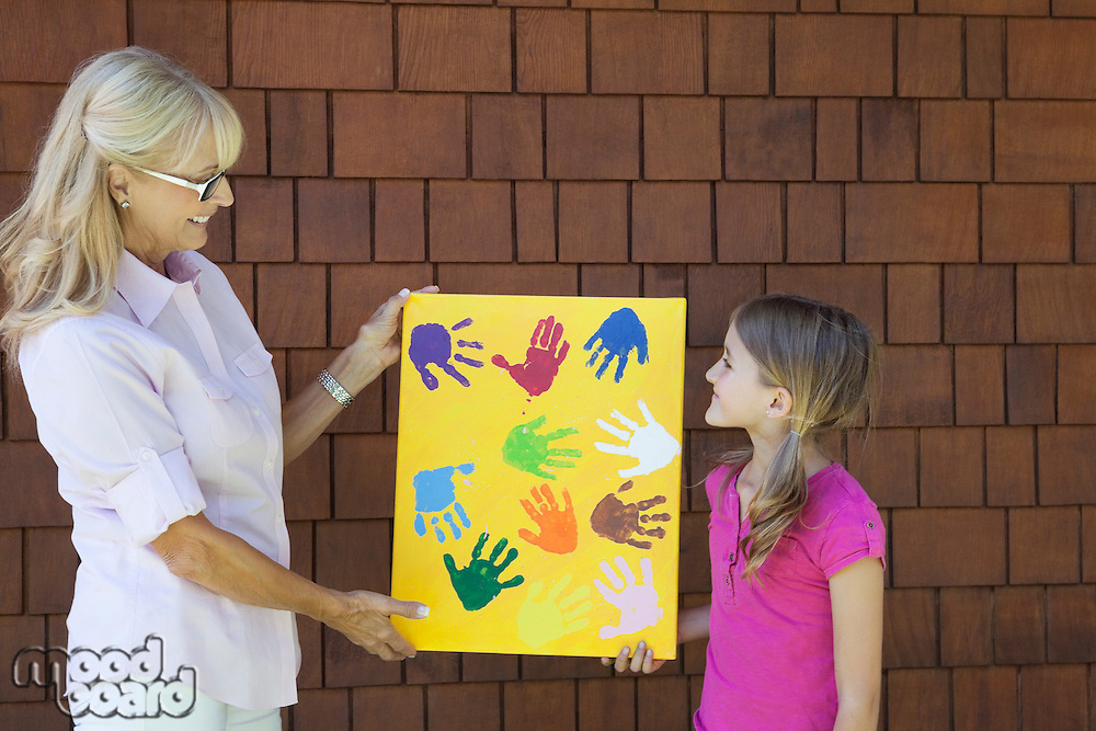 Grandmother and granddaughter showing colorful multiple hand prints against brick wall