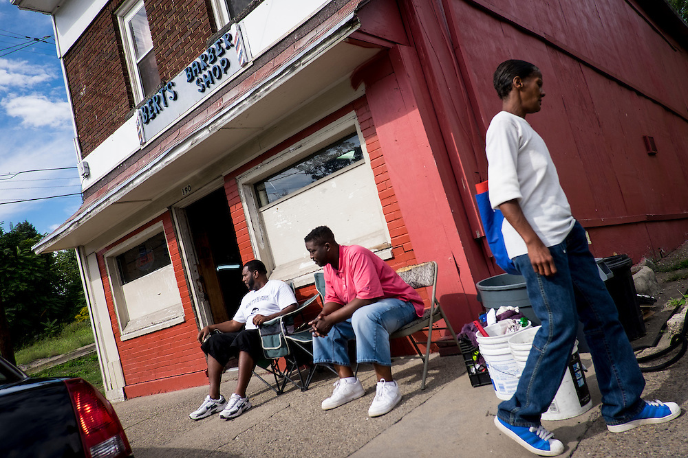 Aliquippa residents hang out in front of Bert's Barber Shop, a mainstay of the Plan 11 neighborhood for 60 years, as they talk about that night's Aliquippa High School homecoming game.
