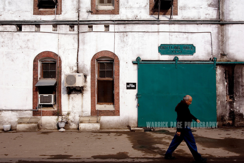 RAWALPINDI, PAKISTAN - DECEMBER 21: A worker walks past the bottling hall at the Murree Brewery, December 21, 2006, Rawalpindi, Pakistan. The brewery boasts the first 20 year-old malt whiskey in the Muslim world, due for release in mid-2007. Established more than a century ago under British Raj, Murree Brewery also is Pakistan's oldest company and one of two breweries in a country under prohibition. Muslims have been banned from drinking alcohol since it was outlawed in 1977, but Christians and Hindus may still buy alcohol. The brewery hopes to export the exclusive whiskey to Europe and the Middle East. (Photo by Warrick Page)