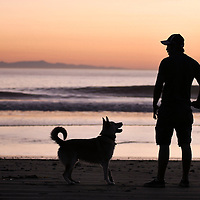A man and his dog play at the beach in Ventura, CA.