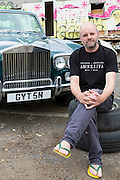 Gavin Turk, artist, photographed with his old Rolls Royce car on wasteland near his East London studio, United Kingdom