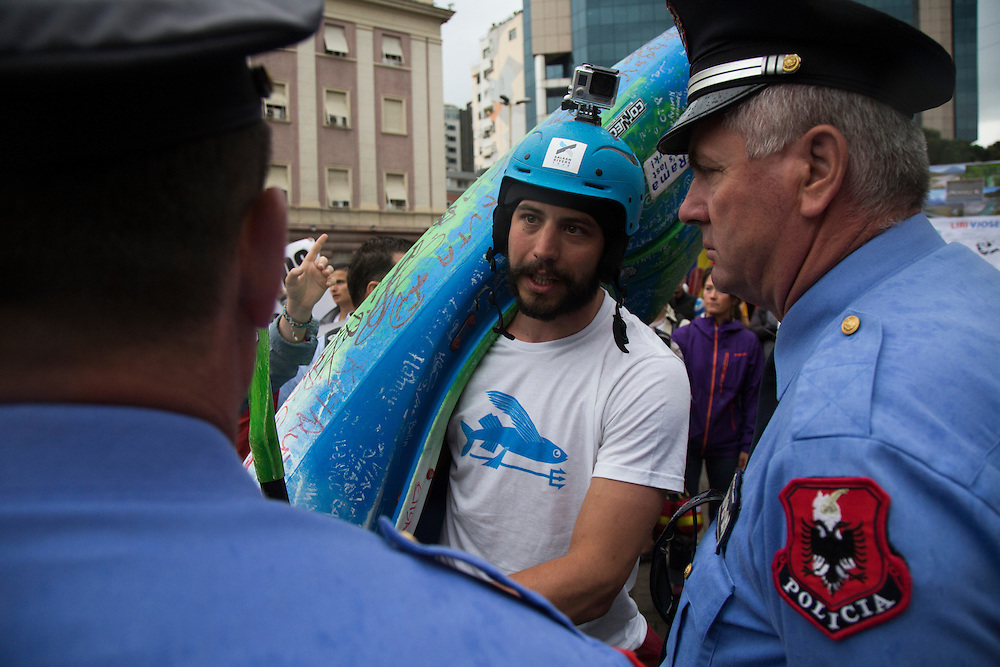 Ron Rozman tries to convince police to allow him to put his kayak, signed by scientists, villagers and environmental activists protesting plans to build dams in the country, on the doorstep of the offices of Edi Rama, Albanian prime minister.