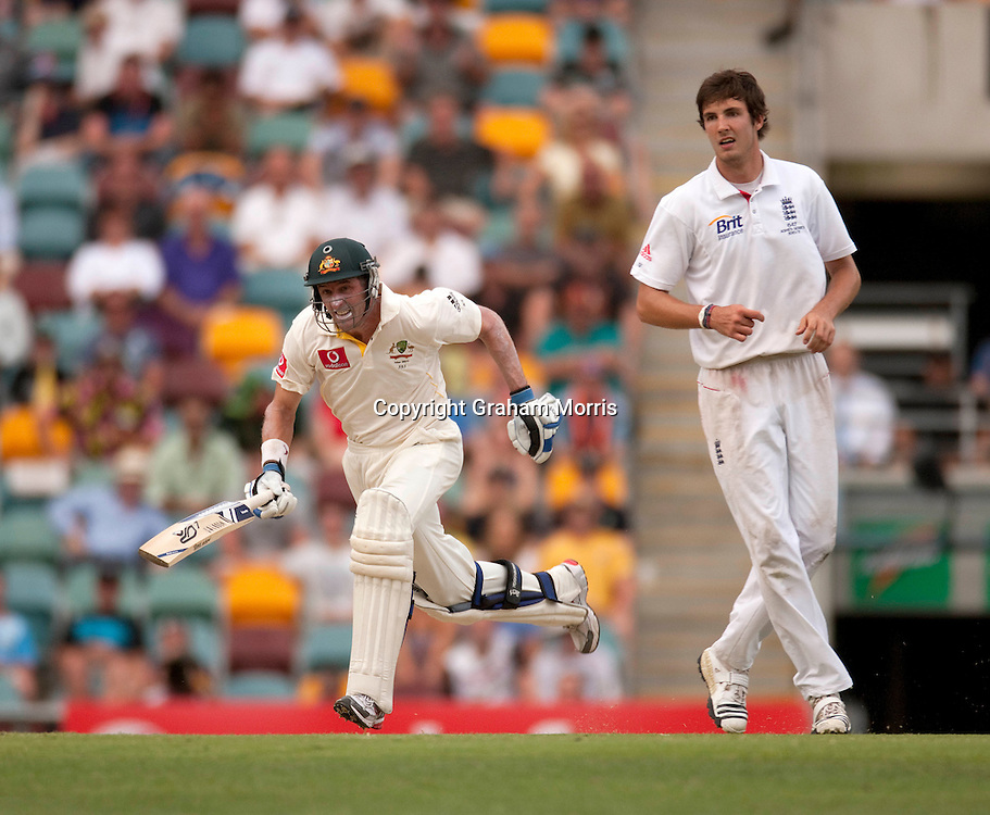 Michael Hussey runs past bowler Steven Finn during the first Ashes Test Match between Australia and England at the Gabba, Brisbane. Photo: Graham Morris (Tel: +44(0)20 8969 4192 Email: sales@cricketpix.com) 26/11/10