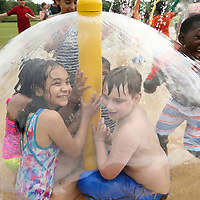 Rankin Elementary School students Krystall Mac, 10, and Dylan Roach, 8, sit under a layer of water with other students as Cedric Bailey, right, 9, breaks through the barrier of water to join them during their Field Day at Veterans Tuesday morning.