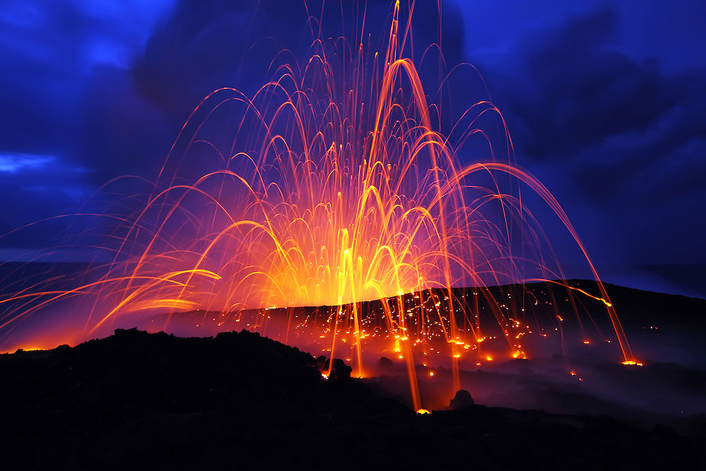 Seawater, forced into the main lava tube by high surf, flashes to steam, generating a huge fiery littoral explosion that sends ejecta skyward.  The glowing bits of lava burn arcing trails against the early morning sky in this 6 second exposure.