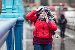 © Licensed to London News Pictures. 08/02/2019. London, UK.  A woman holds onto her scarf as she crosses Tower Bridge during wet and windy weather. Storm Erik is the first named storm of 2019 with gale force winds and wet weather affecting most of the UK today. Photo credit: Vickie Flores/LNP