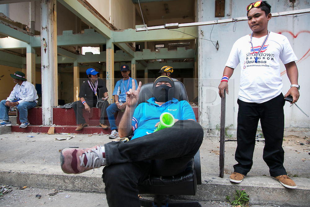 © Licensed to London News Pictures. 17/01/2014. Anti-Goverment supporter makes a peace sign while sitting down in an abandoned apartment complex  after a suspect threw an explosive device injuring eight people during an anti-government street rally on January 17, 2014 in Bangkok, Thailand. Anti-government protesters launch 'Bangkok Shutdown', blocking major intersections in the heart of the capital, as part of their bid to oust the government of Prime Minister Yingluck Shinawatra ahead of elections scheduled to take place on February 2. Photo credit : Asanka Brendon Ratnayake/LNP