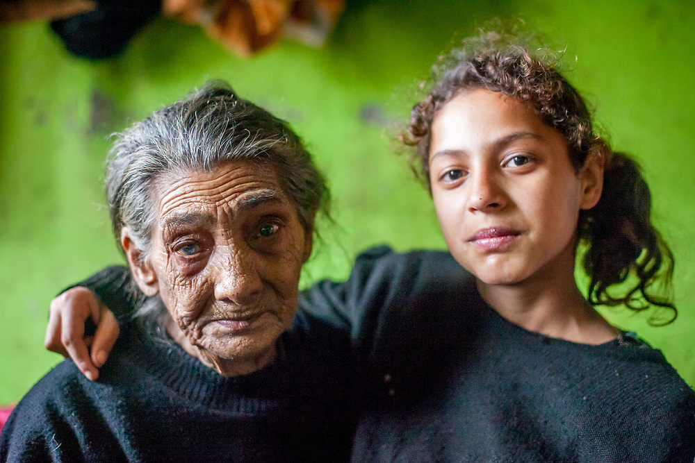 """Portrait of Maria (85) - the oldest inhabitant of the Roma settlement """"Budulovska Street"""" with 11 years old Celestina. """"Budulovska Street"""" is a segregated Roma settlement located about 2,5 km behind the city of Moldava nad Bodvou close to Kosice in east Slovakia. The city has roughly 11200 inhabitants, about 1980 (18%) of them have Roma ethnicity and around 800 are living at the segregated settlement 'Budulovska Street' (2014)."""