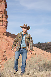 cowboy walking through a rugged landscape