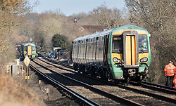 © Licensed to London News Pictures. 17/02/2018. Horsham, UK. The remains of a car is seen further up the track near the level crossing where the southbound train (seen at right with damage to the lower front)  remains stationary after two people were killed near the village of Barns Green. Photo credit: Peter Macdiarmid/LNP
