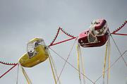 Ferris wheel cars lit by afternoon sun against storm clouds.