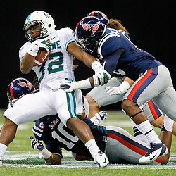 September 22, 2012; New Orleans, LA, USA; Ole Miss Rebels players tackle Tulane Green Wave running back Dante Butler (32) during the second half of a game at the Mercedes-Benz Superdome. Ole Miss defeated Tulane 39-0. Mandatory Credit: Derick E. Hingle-US PRESSWIRE