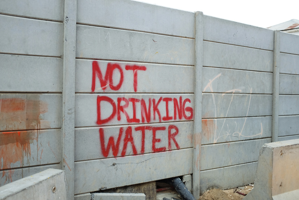 A sign on the wall of a construction site in Woodstock, Cape Town warns that water in use is not drinkable.