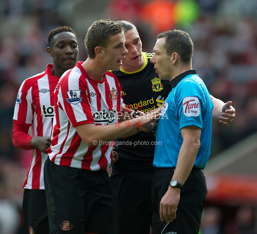 SUNDERLAND, ENGLAND - Sunday, March 20, 2011: Liverpool's Andy Carroll and Sunderland's Jordan Henderson speak to referee Kevin Friend during the Premiership match at the Stadium of Light. (Photo by David Rawcliffe/Propaganda)