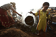A girl carries a bucket as she heads to go fetch water at a wood charcoal production site on the outskirts of San Pedro, Bas-Sassandra region, Côte d'Ivoire on Sunday March 4, 2012. Men, women and children - who don't go to school - work here seven days a week.