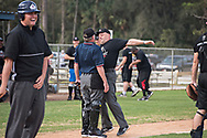 Plate Umpire Charlie Jennette gets playfully chest bumped by Kevin Macho, who was arguing a call, during the exhibition game on the last day of Umpire School.