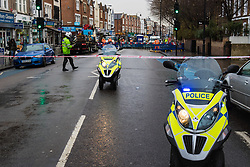 Police man a cordon closing Tooting Broadway to traffic as workers clean up and prepare to dig up a large burst water main just yards from the entrance to Tooting Broadway station in South London. London water supply companies are battling a series of burst mains following the recent cold weather brought on by 'The Beast From The East'. London, March 07 2018.