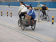 two girls riding a bicycle cart Beijing China