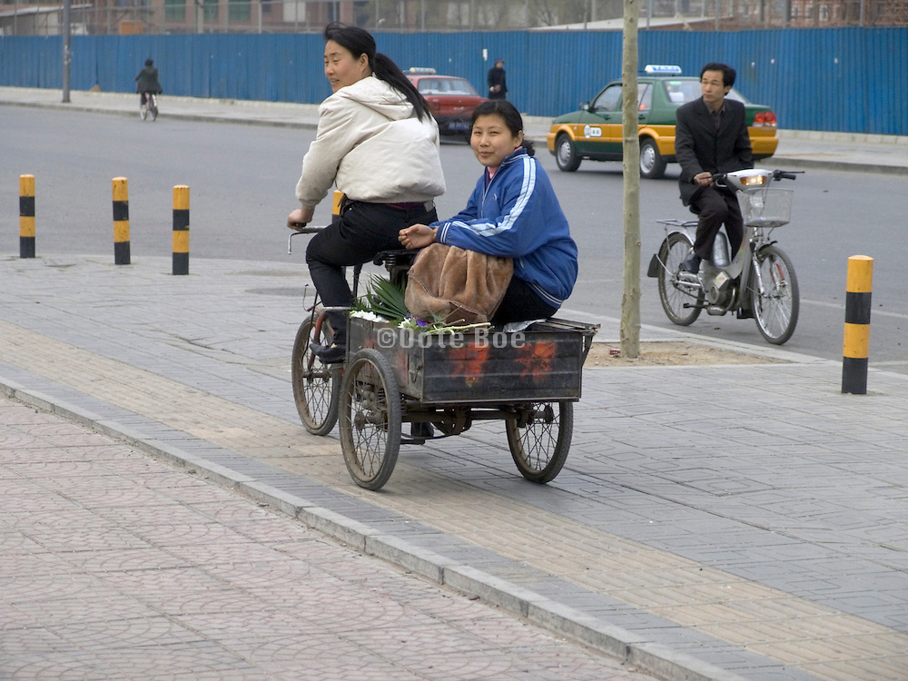 two girls riding a bicycle cart Beijing China