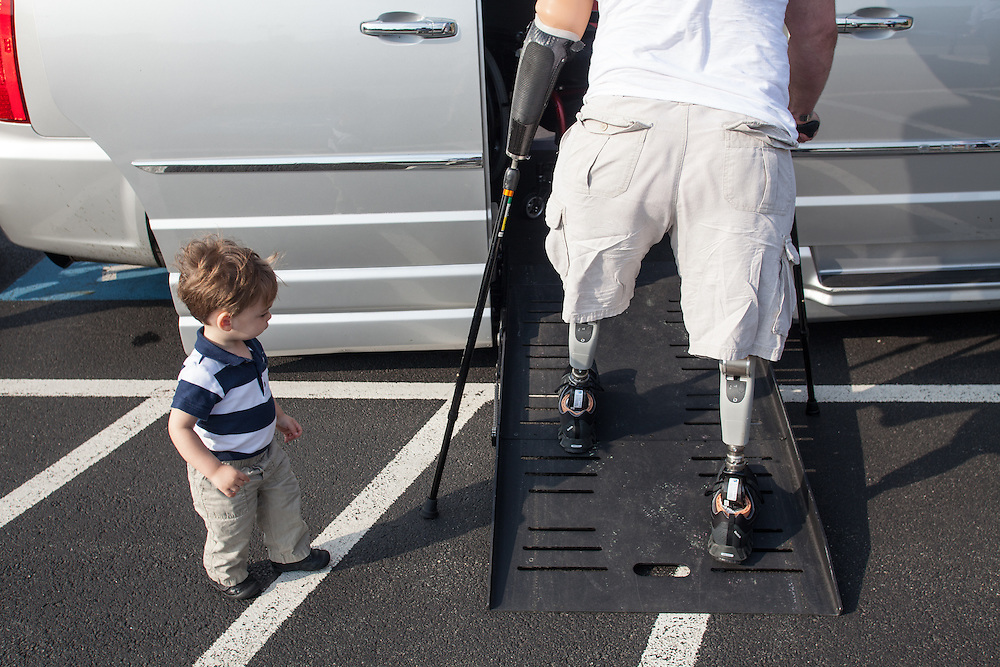 Injured Air Force Master Sgt. Joseph Deslauriers Jr. walks up a ramp into his customized van on prosthetic legs, as his 17 month old son Cameron watches, after a lunch with his family in Franklin, MA, during a visit home on Monday, May 20, 2013. In 2011, Deslauriers lost both of his legs and part of an arm after stepping on an explosive device while stationed in Afghanistan. He is currently rehabbing at Walter Reed Army Medical Center.  (Matthew Cavanaugh for The Washington Post)