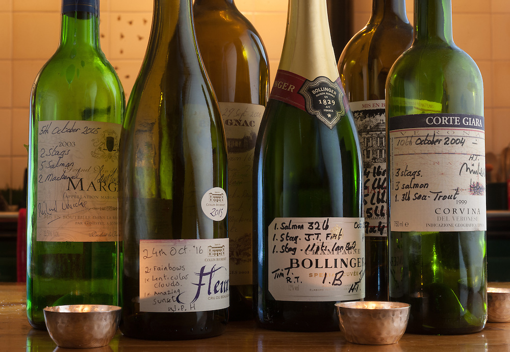 """Wine bottles contrasting """"catches"""" of country sportsmen and photographers, Torridon, Scotland"""